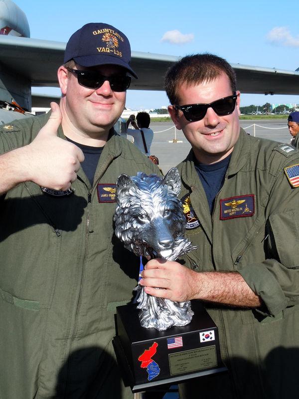 トロフィを誇らしげに掲げる、VAQ-136のデマースマン少佐(左)とマックリン大尉(右)