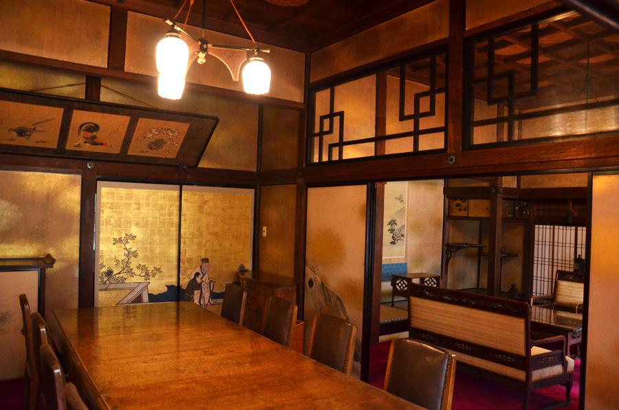 伝統的な和室に椅子とテーブルが鎮座する食堂。客間との間には月の字欄間