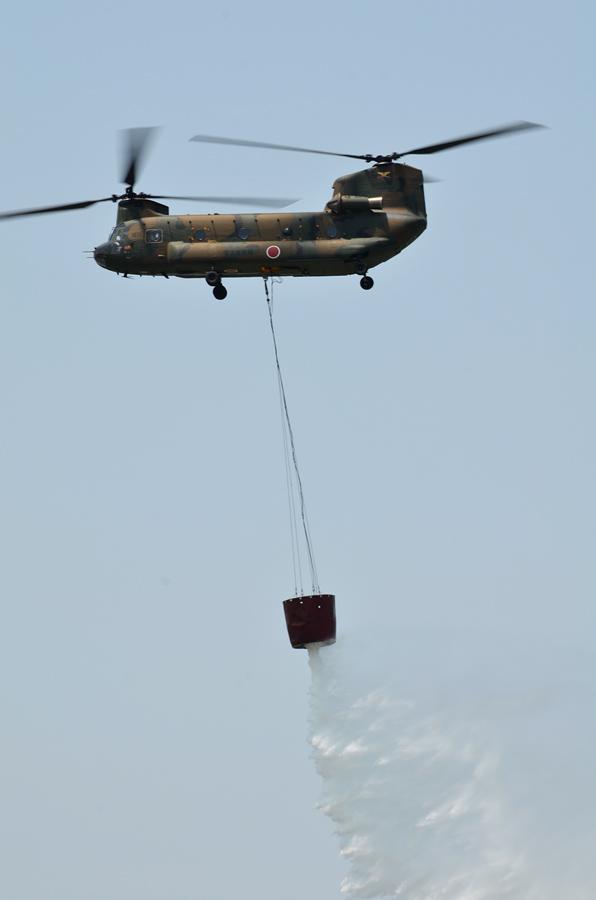 吊り下げたバケットから放水するCH-47J
