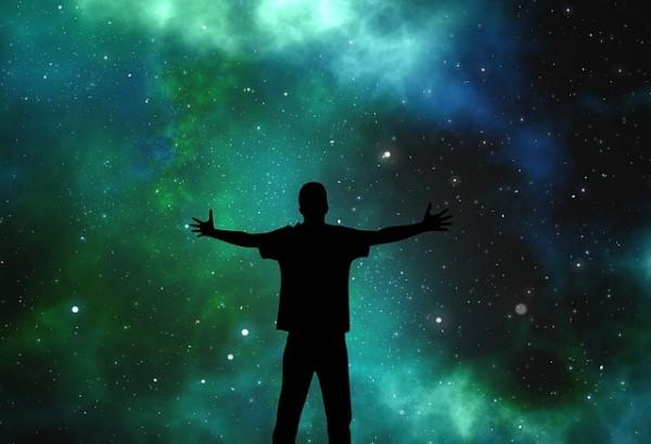 夜空に手を広げる男性