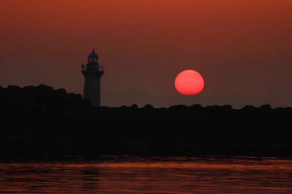 白い灯台と真昼の円月の名残