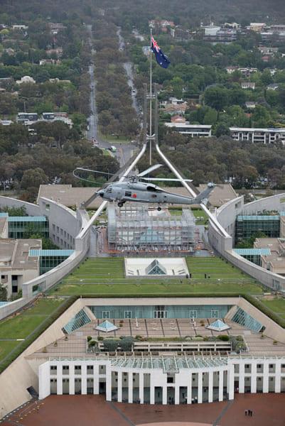連邦議会議事堂上空を飛ぶS-70B-2(画像:(c) Commonwealth of Australia)