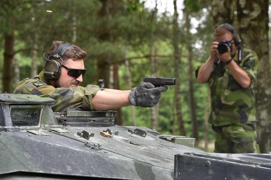 Strv.122の砲塔からハンドガンを撃つスウェーデンの戦車兵