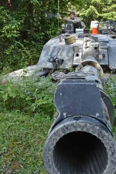 チャレンジャー2の砲塔からハンドガンを撃つイギリスの戦車兵