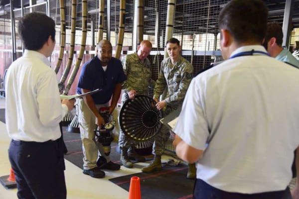 日本からの視察団に空中給油ドローグを見せる空軍兵(画像:USAF)