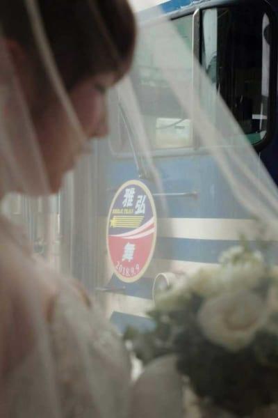 花嫁とホームでの撮影用ヘッドマークをつけたブライダルトレイン(撮影:かつかれいさん)