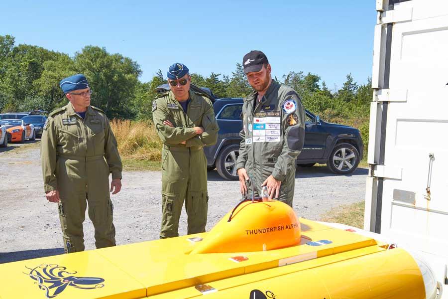 潜水調査艇を前に打ち合わせをするプロジェクトスタッフとカナダ空軍のスタッフ(Photo:RCAF)