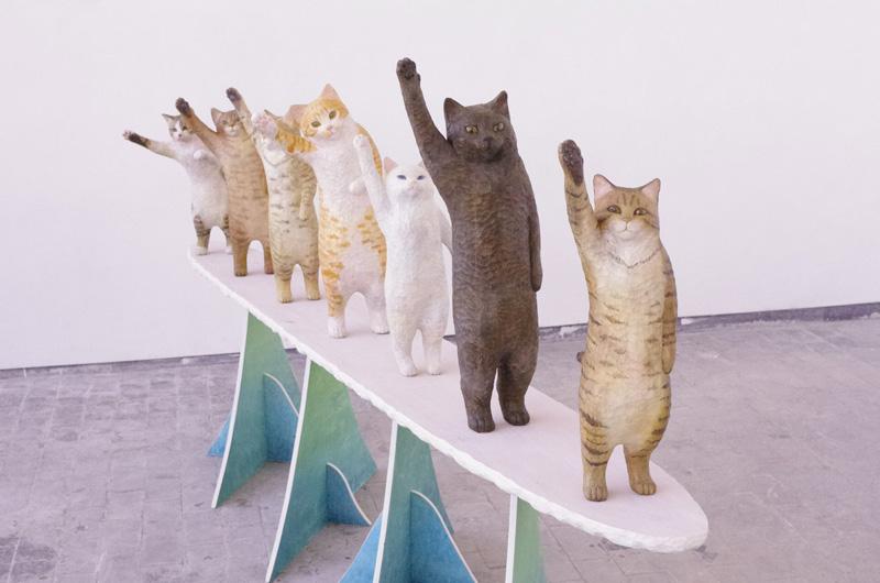 「ハイタッチ!」と肉球を上げる7匹の猫たち 木彫作品「high-seven」
