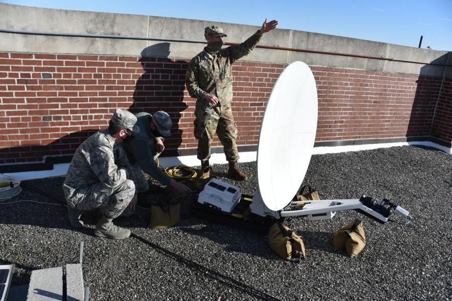 通信用パラボラアンテナを設置する兵士(Image:U.S. Air National Guard)