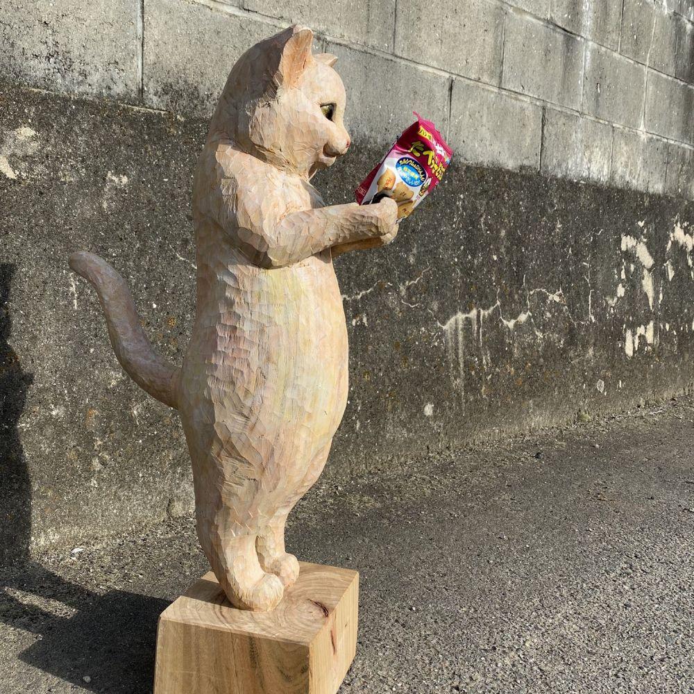 たべっ子どうぶつ見つめる木彫り猫 クスッと笑えるその正体はスマホスタンド