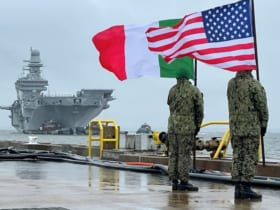 ノーフォークの岸壁でイタリアとアメリカの国旗を掲げカヴールを迎えるアメリカ兵(Image:イタリア海軍)