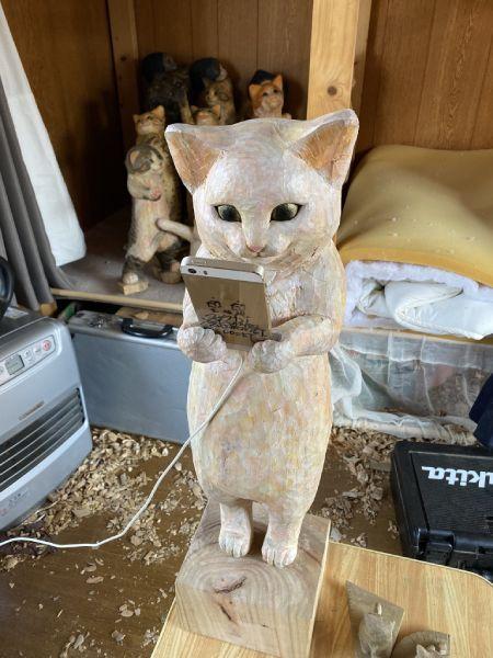 「猫」の正体は、実はスマートフォン置きの木彫りアート。