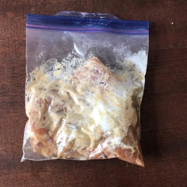 寝かせたモモ肉に小麦粉を加えて揉み込む
