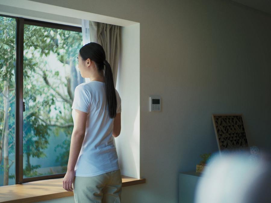 窓を開けたいけれど蚊が入ってくることを恐れてためらっている女性