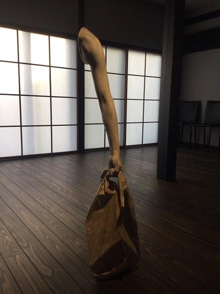 空間から腕?腕だけ消し忘れた透明人間? レジ袋と腕をかたどった木彫りの彫刻