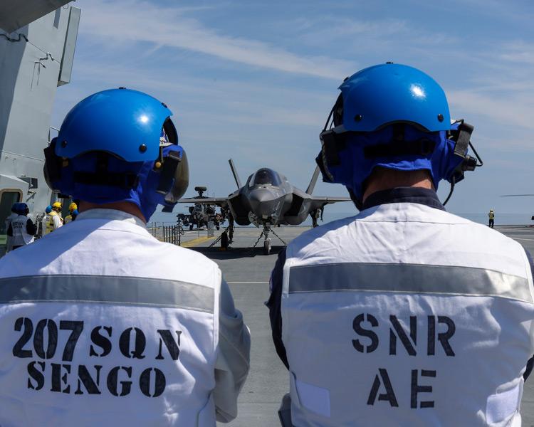 着艦を見守るプリンス・オブ・ウェールズ乗組員と第207飛行隊の兵士(Image:Crown Copyright)