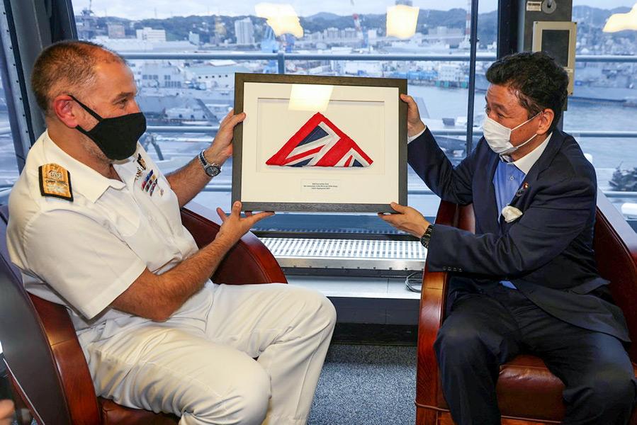 イギリス軍艦旗(ホワイト・エンサイン)を贈られる岸防衛大臣(Image:Crown Copyright)
