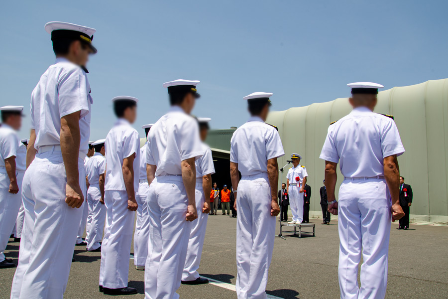 拳を握って「気をつけ」の姿勢を取る海上自衛官